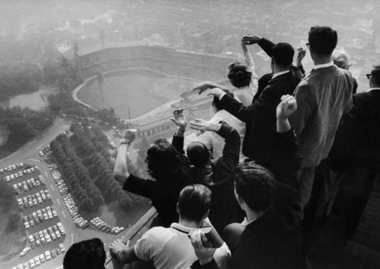 Univ. of Pittsburgh students cheering wildly from atop Cathedral of Learning on school's campus as they look down on Forbes Field where the Pittsburgh Pirates are winning their first World Series in 35 yrs. against the NY Yankees. George Silk